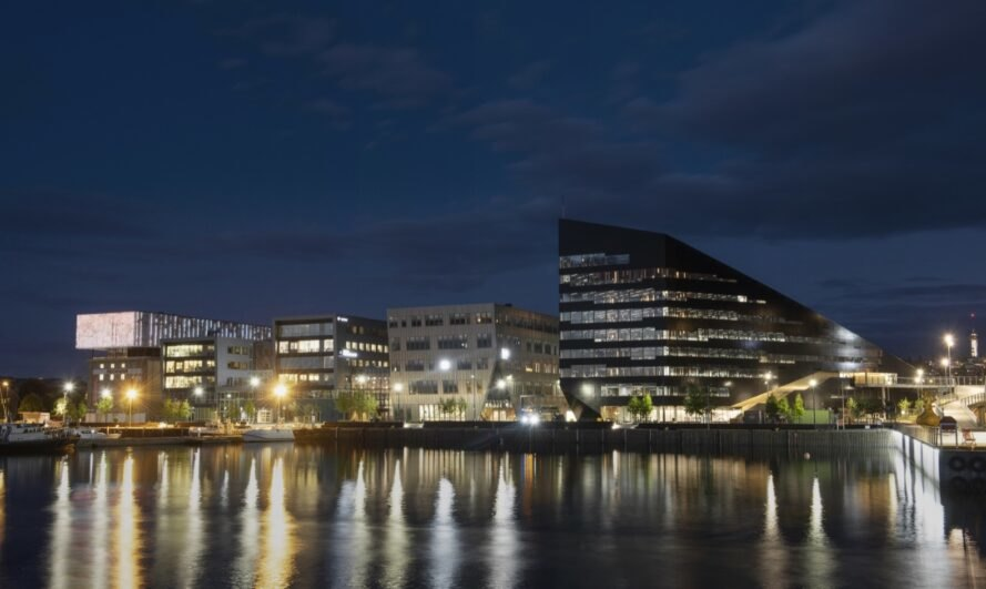 dark metal-clad geometric building and traditional office buildings near water lit up at night