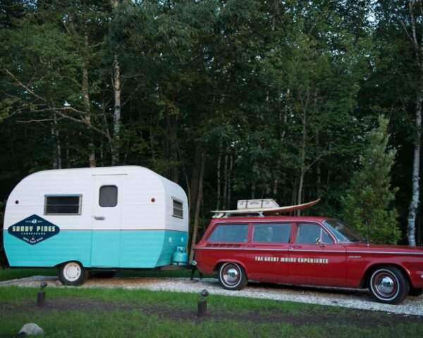 little camper being pulled by a red station wagon