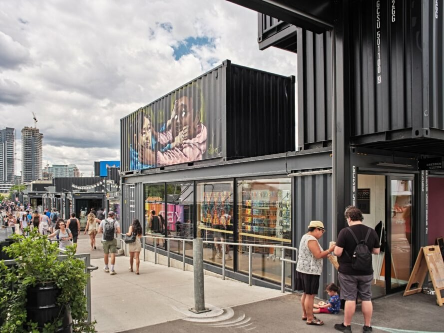 black shipping container market with painted murals on walls
