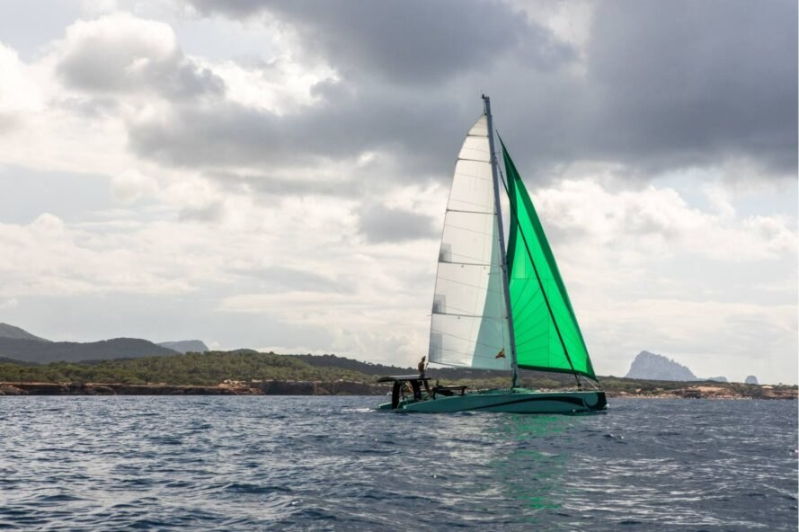 zero-emissions catamaran with green sail on the water