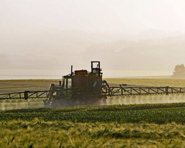 tractor spraying farm fields with herbicide