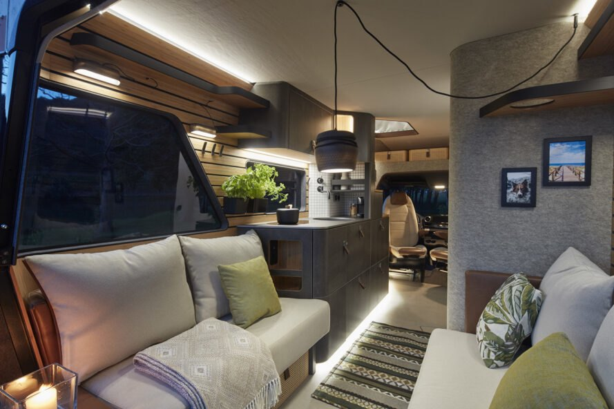 rendering of camper van with white sofas and black kitchen