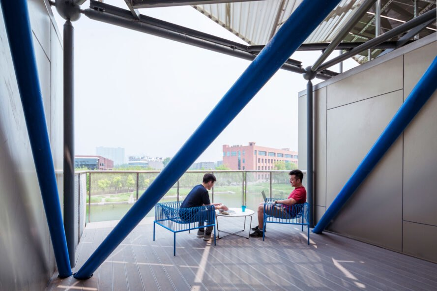 two people sitting on blue chairs on outdoor patio
