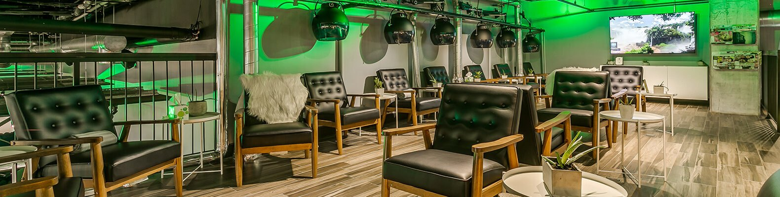 salon with black chairs and green lights