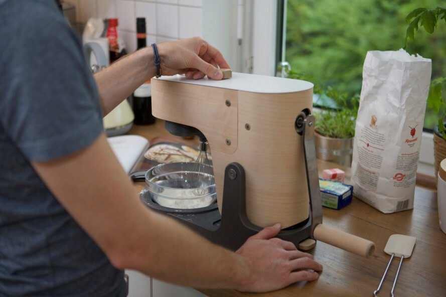 person turning a knob on wooden stand mixer