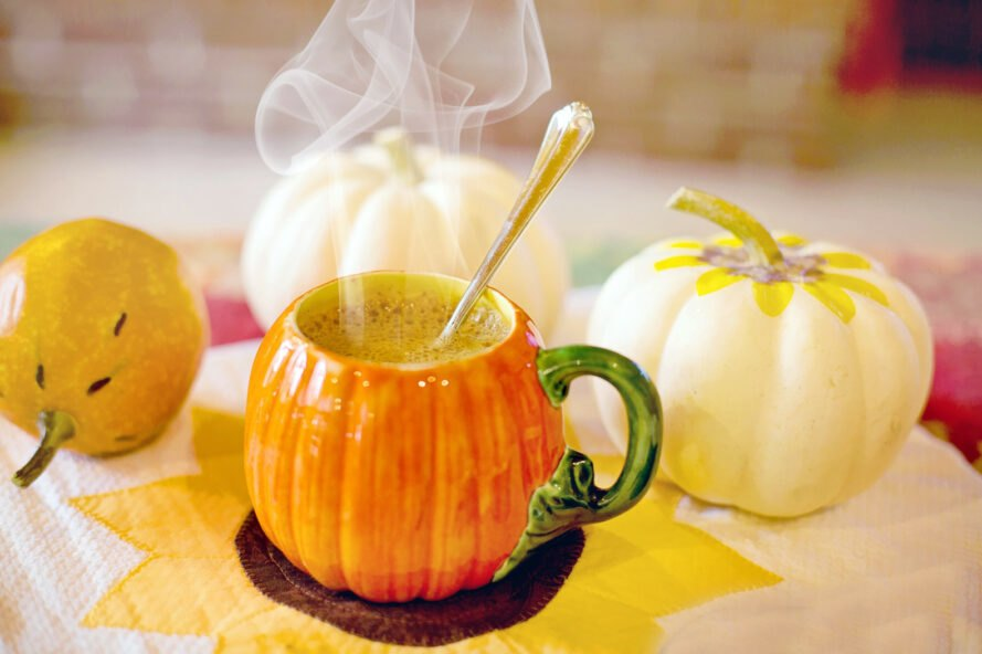 steaming orange latte in a pumpkin mug