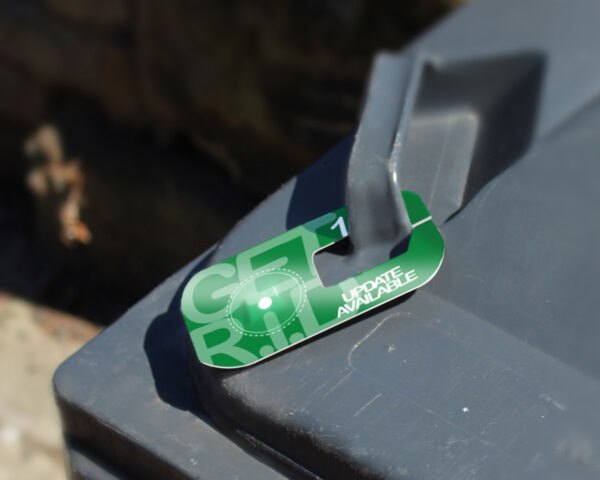 green tag attached to a garbage bin