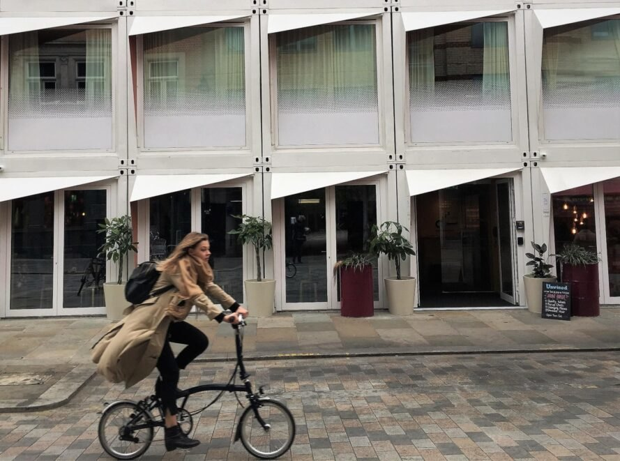 woman riding her bike past a shipping container hotel