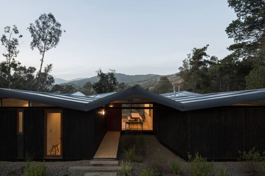 low-rise home with zigzag metal roof all lit up at night