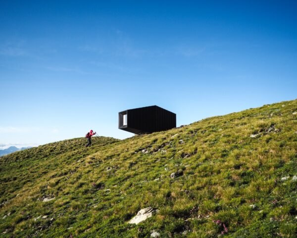 black mountain shelter high in mountains surrounded by greenery