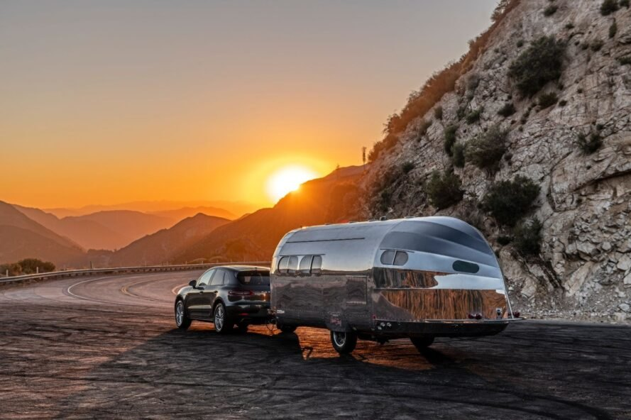 sun rising over mountains and reflecting off an aluminum travel trailer