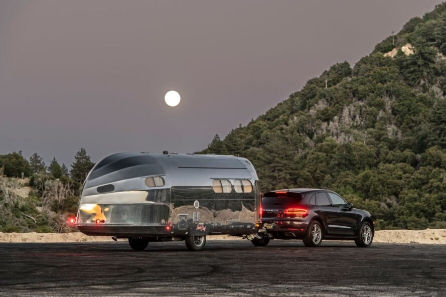 aluminum travel trailer hitched to an SUV