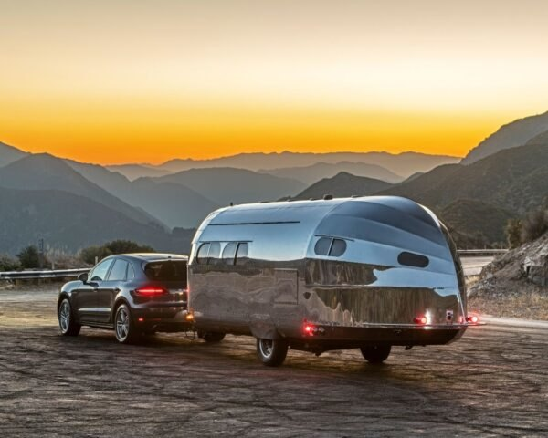 aluminum-clad camper being towed by SUV