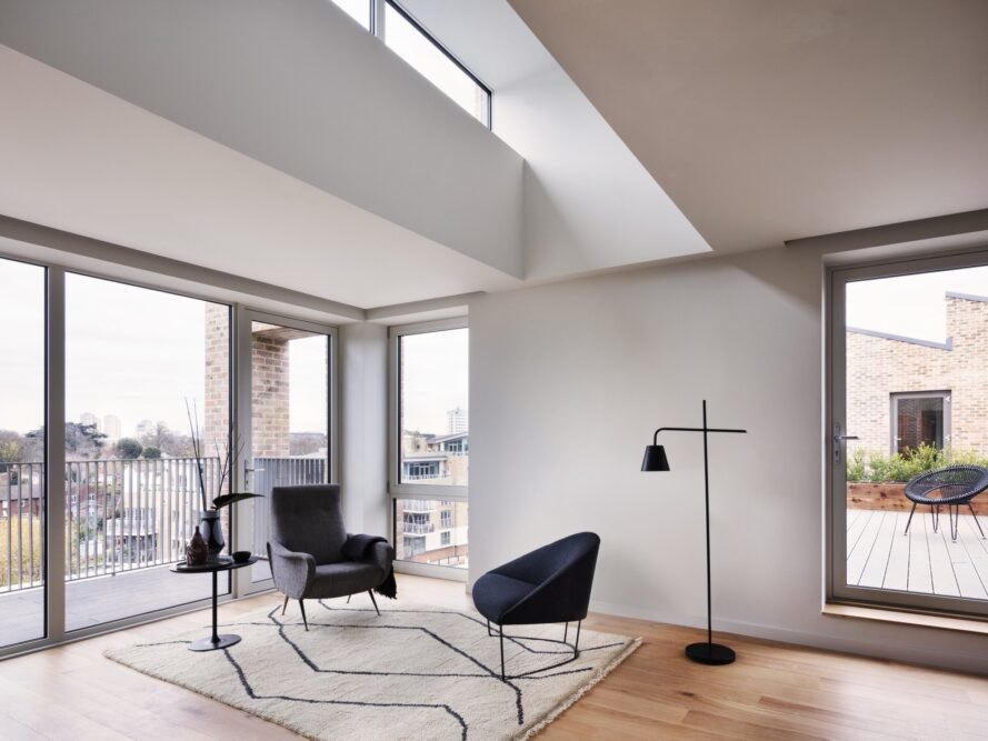 living area with large windows and two dark chairs