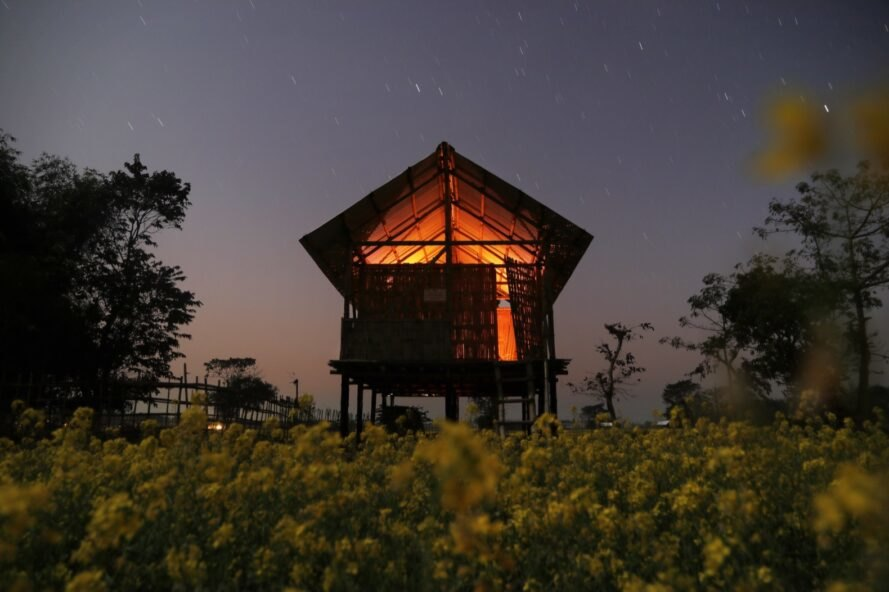 bamboo gabled home lit from within at dusk