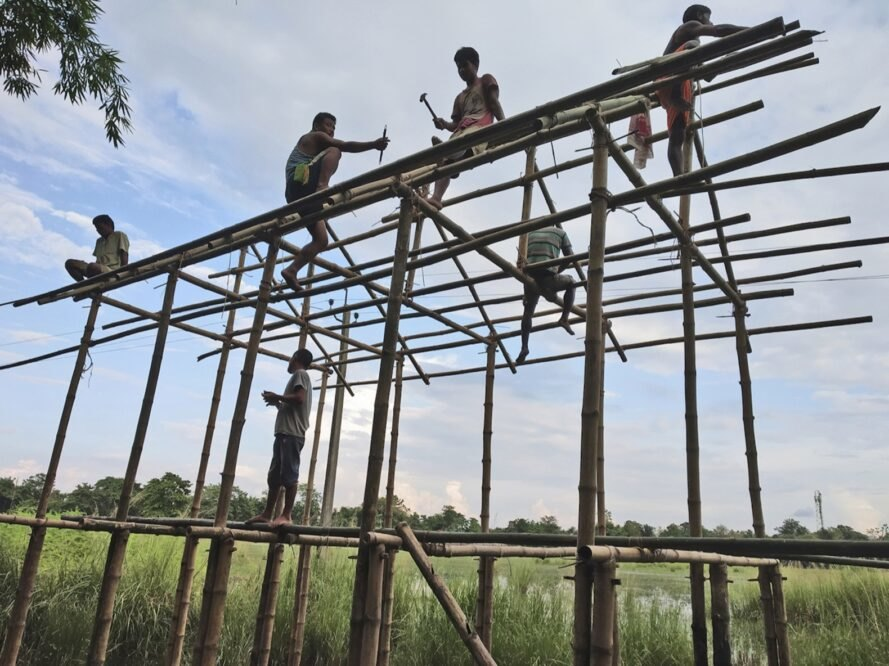 people building a home from bamboo