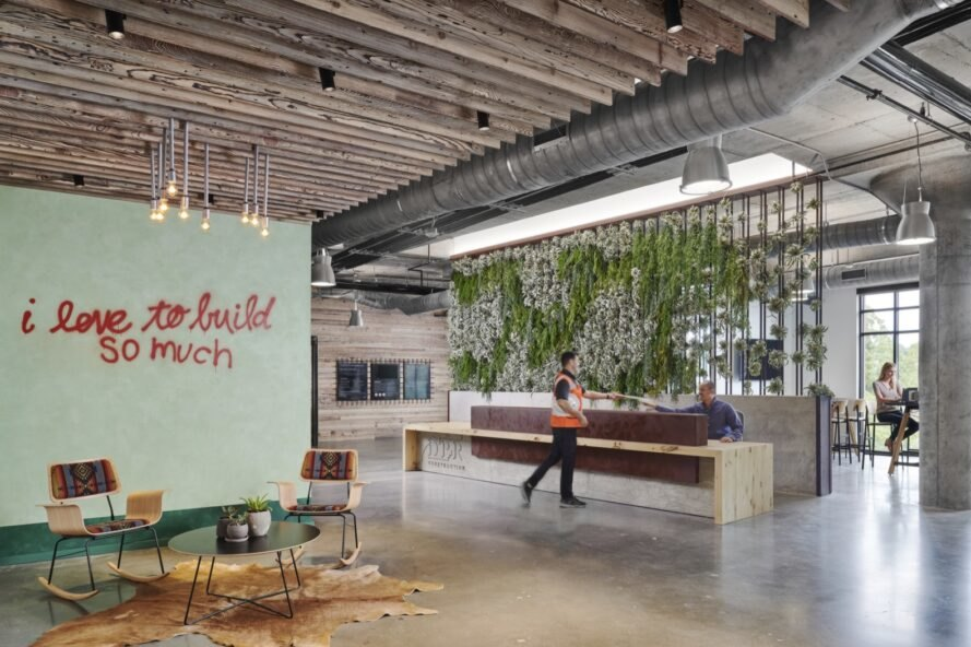 "Light green wall in industrial-style office that reads ""I love to build so much"""