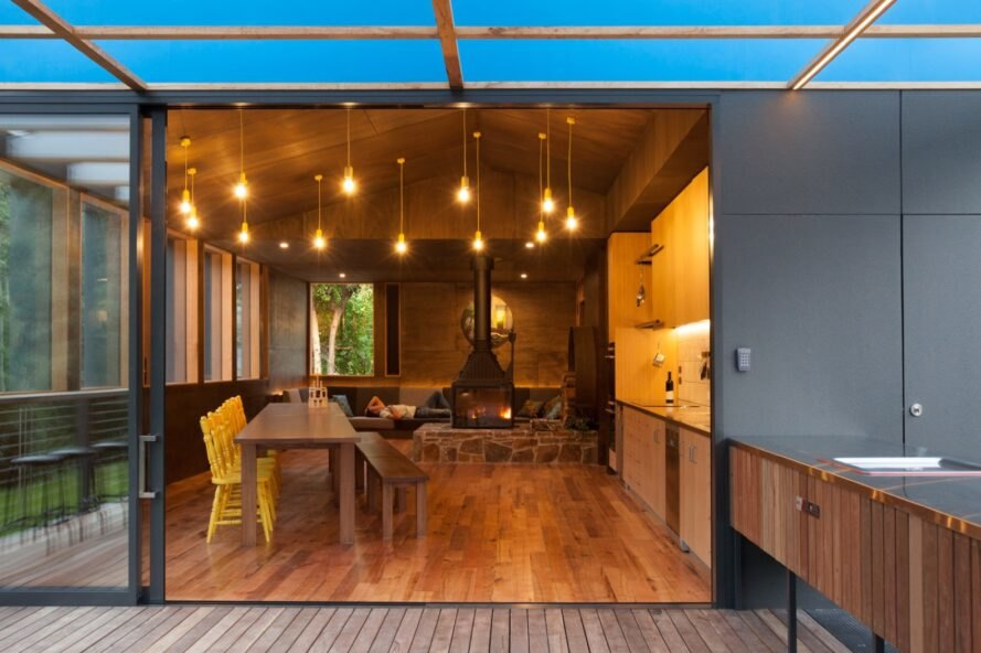 wood-lined dining and kitchen area that is open to outdoor deck