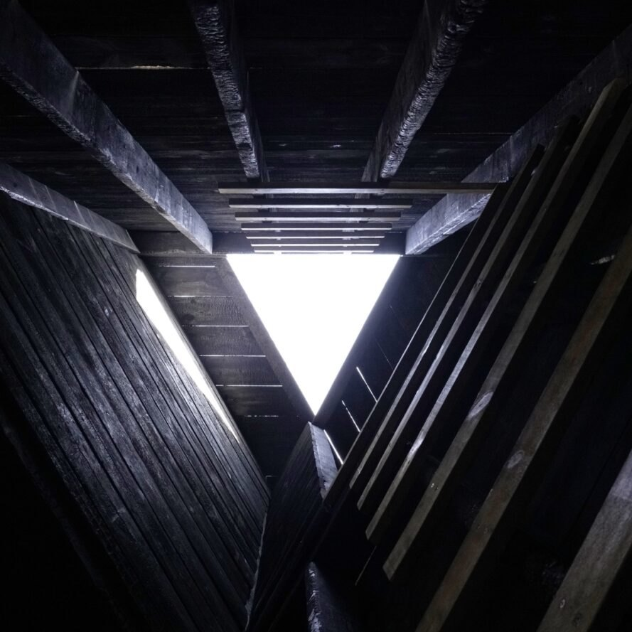triangular skylight at the top of a charred wood pavilion