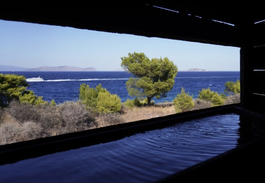 cut-out in a charred wood pavilion revealing views of water and trees