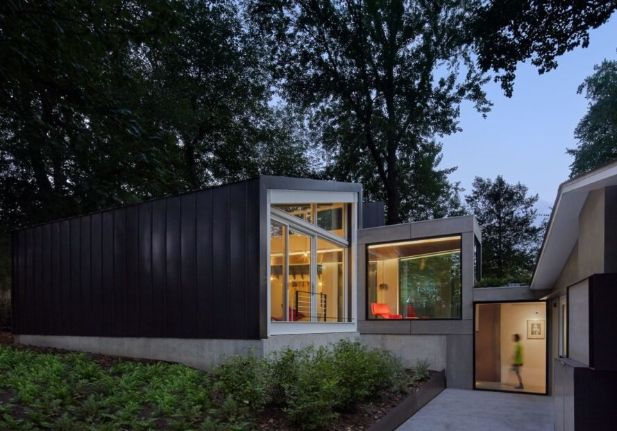 home with dark exterior and a glass wall