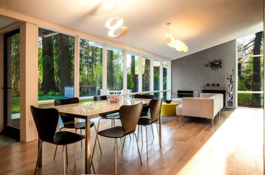 wood dining table and black chairs in room with glass walls