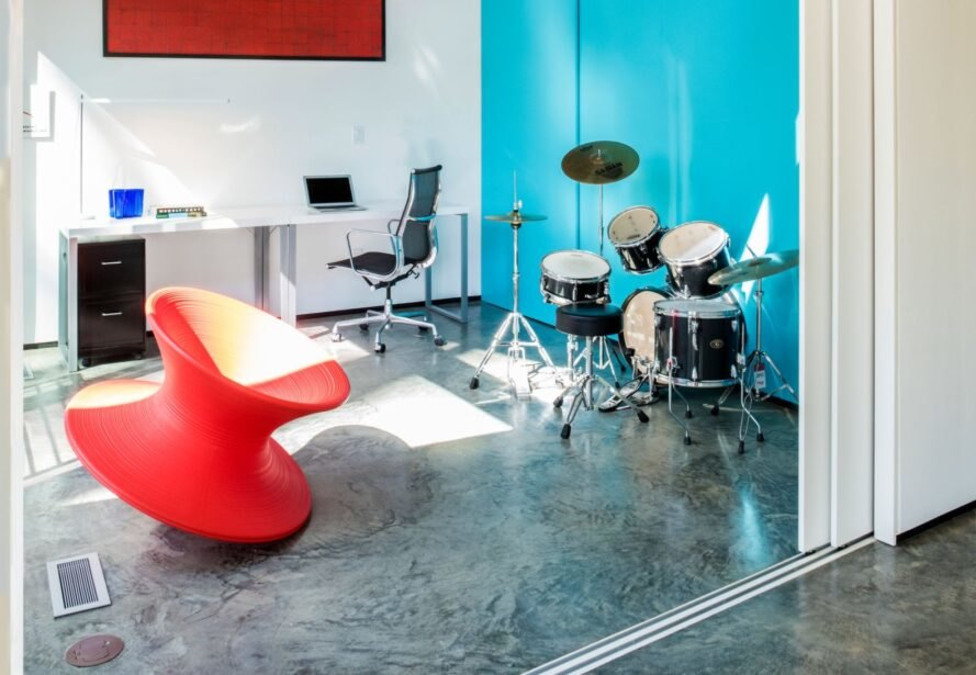 music room with blue walls, red chairs and a drum set