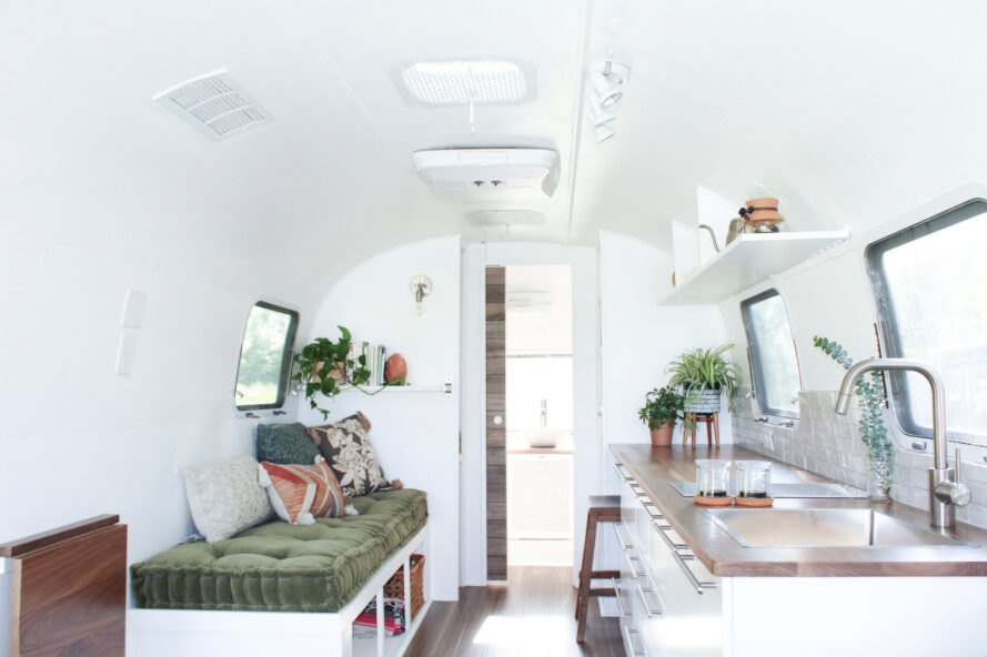 green bench across wood and white kitchen inside an Airstream