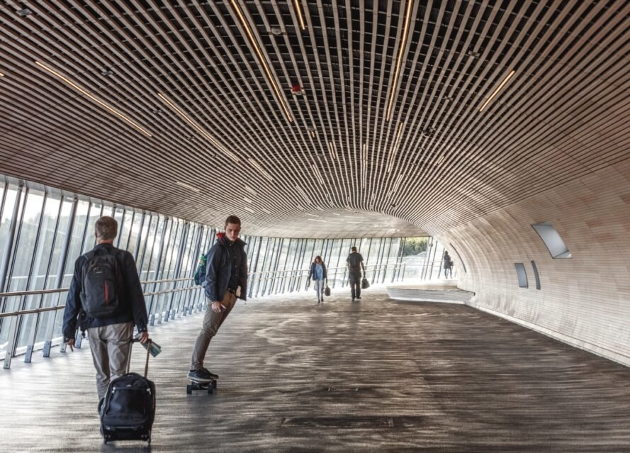 people skateboarding and walking through tube-like bridge