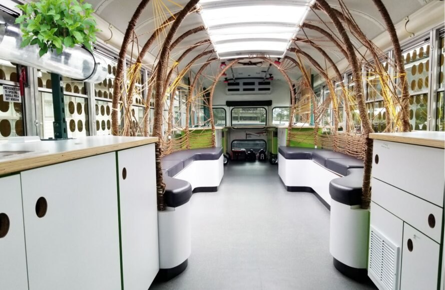 bus interior with long benches and rope arches