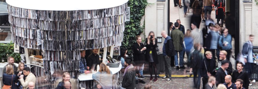 people surround pavilion made from paper waste