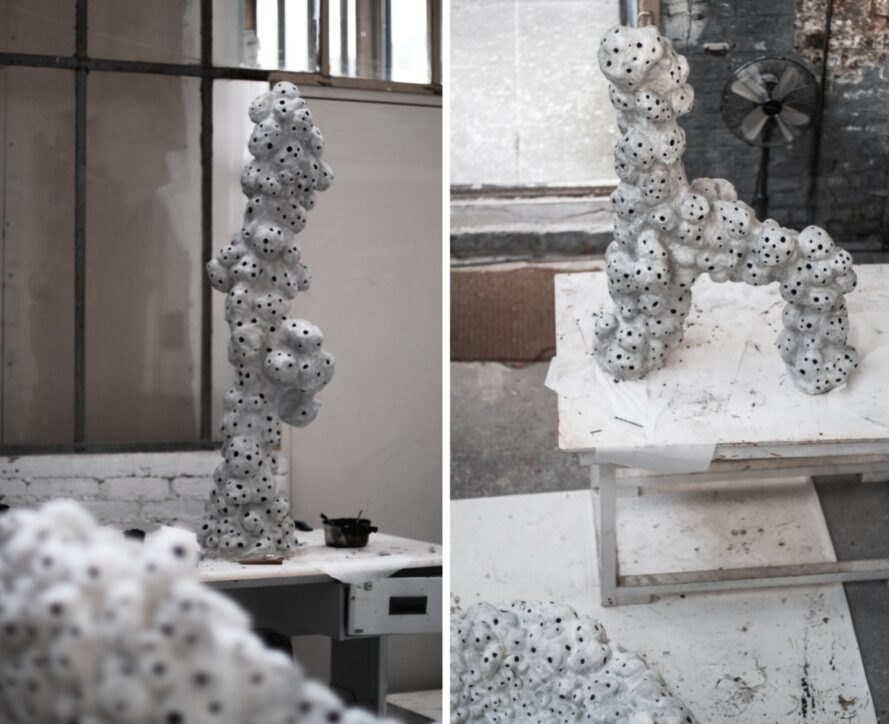white sculptures with holes on display