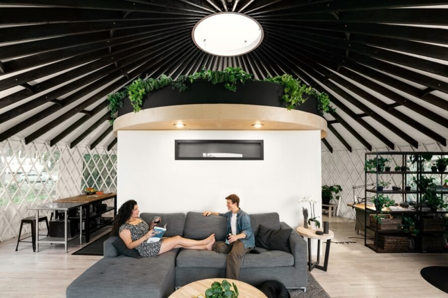 couple sitting on gray sofa in round room with a skylight