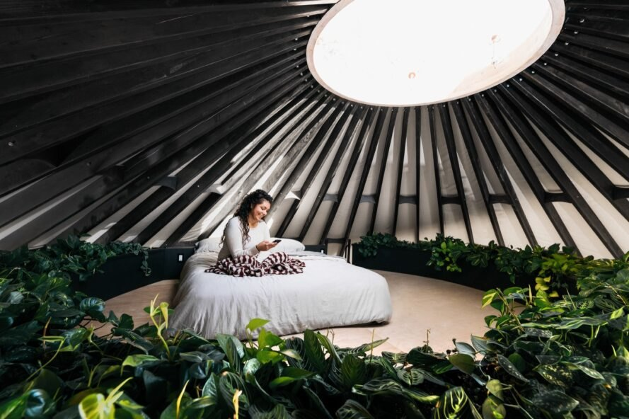 person sitting on bed in a loft under a round skylight