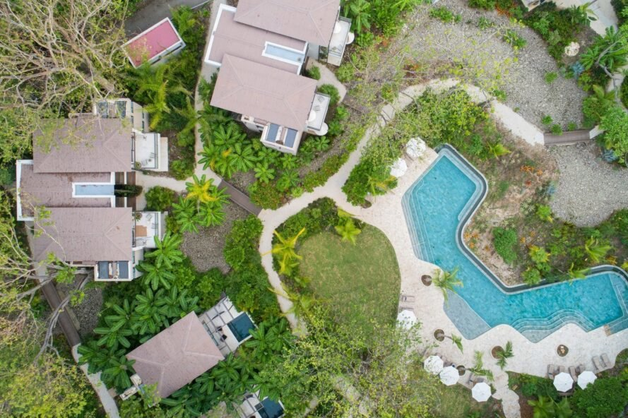 aerial view of beachfront hotel bungalows and swimming pool