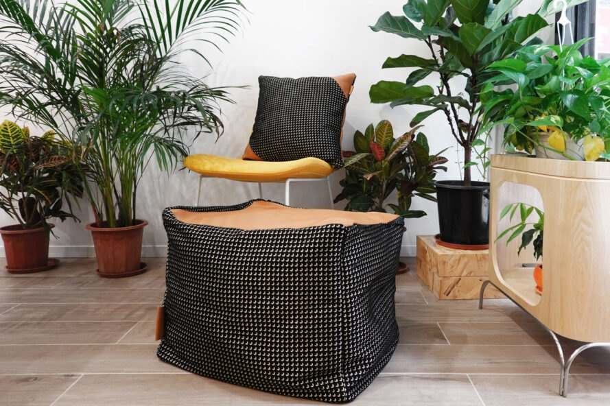tan leather and black and white fabric pillow on a white chair in room filled with plants