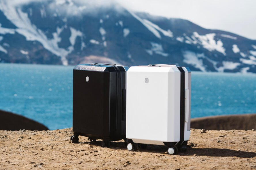 White suitcase and black suitcase with lake in background