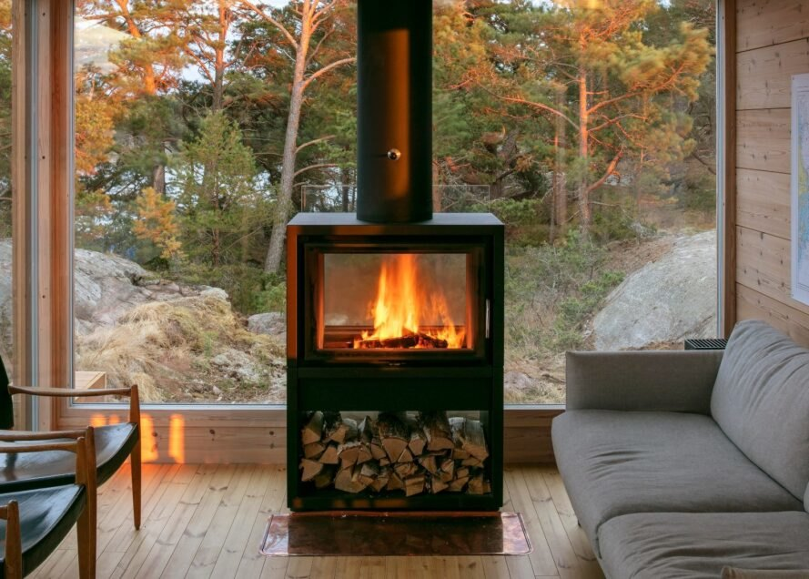 wood-burning stove against glass wall of a cabin