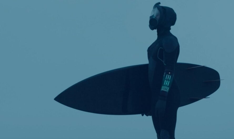 man in black wetsuit with surfing board