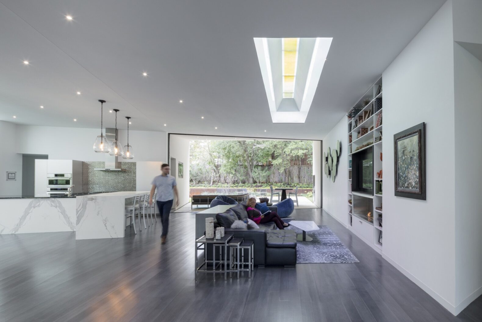 open-plan living area with gray sofa, white kitchen and skylights