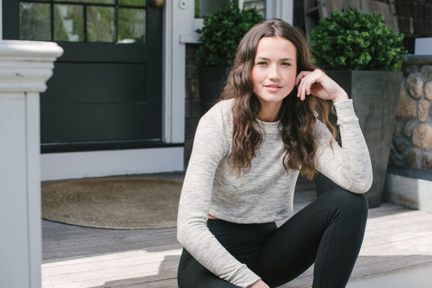person sitting on a porch and wearing sweater and leggings