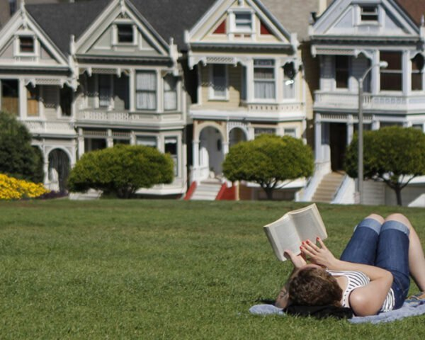 Person lying in grass reading a book in San Francisco
