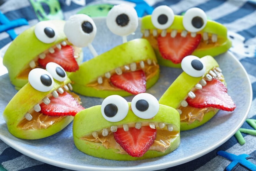 apples, strawberries and sunflower seeds arranged into a monster face