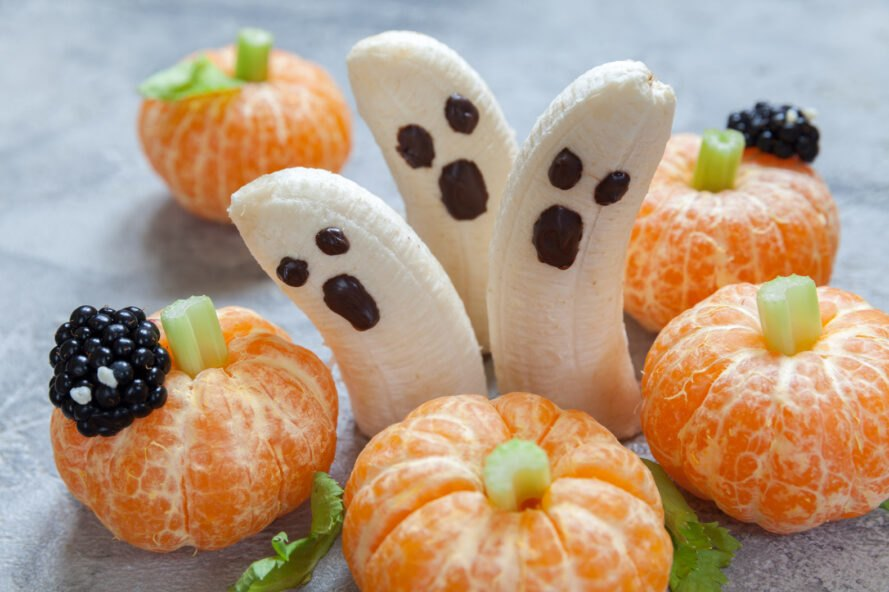 bananas with chocolate ghost faces and mandarin oranges with celery stems to look like pumpkins