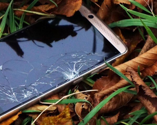 broken phone on a pile of leaves