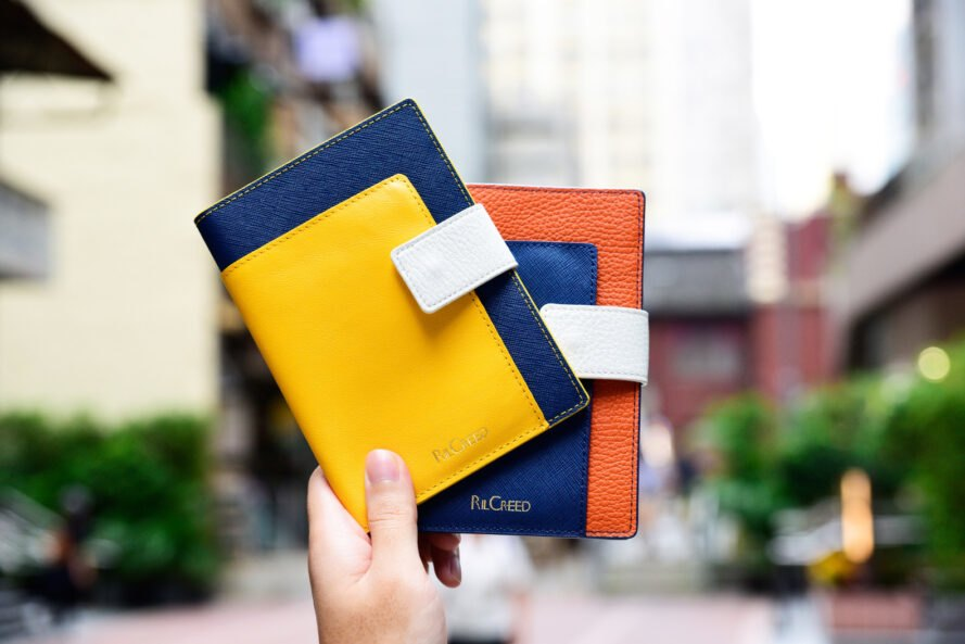 person holding colorful leather passport holders