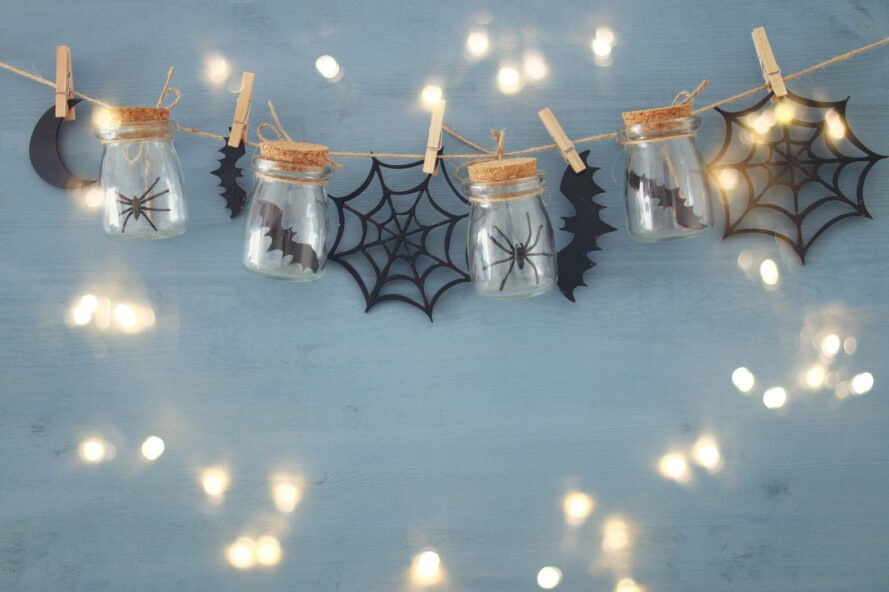 glass jars with toy spiders and bats on a line with paper bats and spider webs