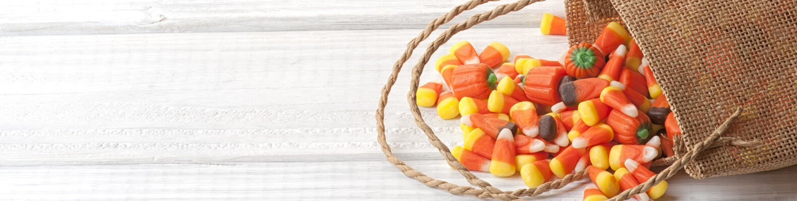 burlap bag of candy corn and pumpkins on white table