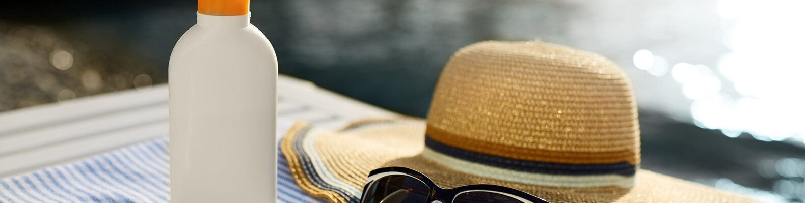 sunscreen, glasses and a hat by water