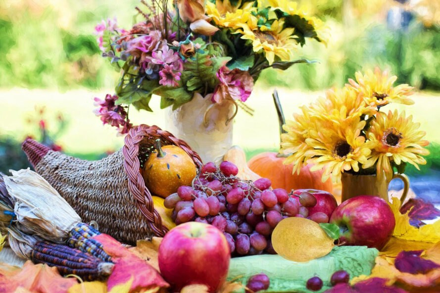 cornucopia filled with fruits on a table near vases of fresh flowers